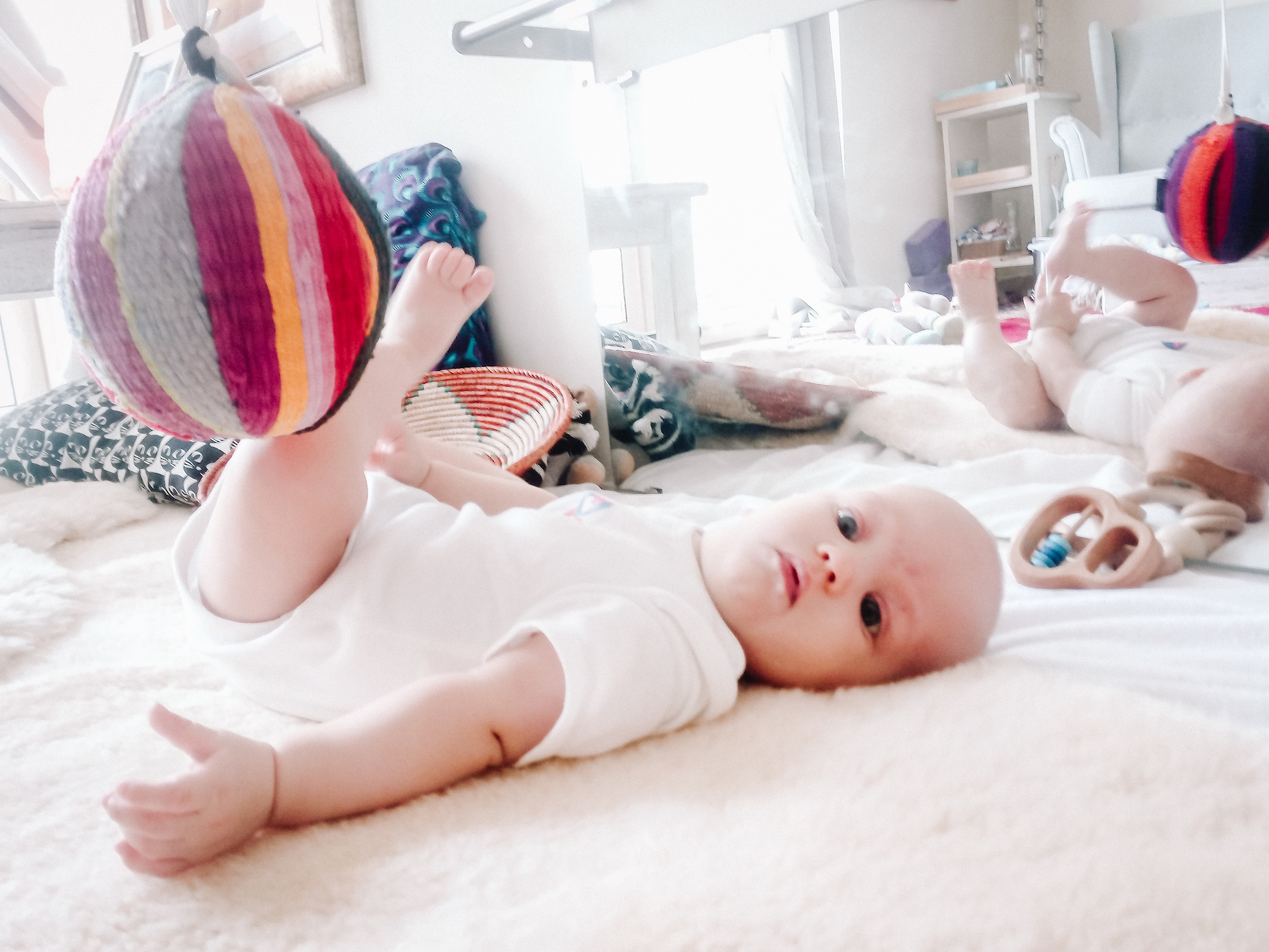 Five month old baby lying on sheepskin next to floor mirror kicking a ball