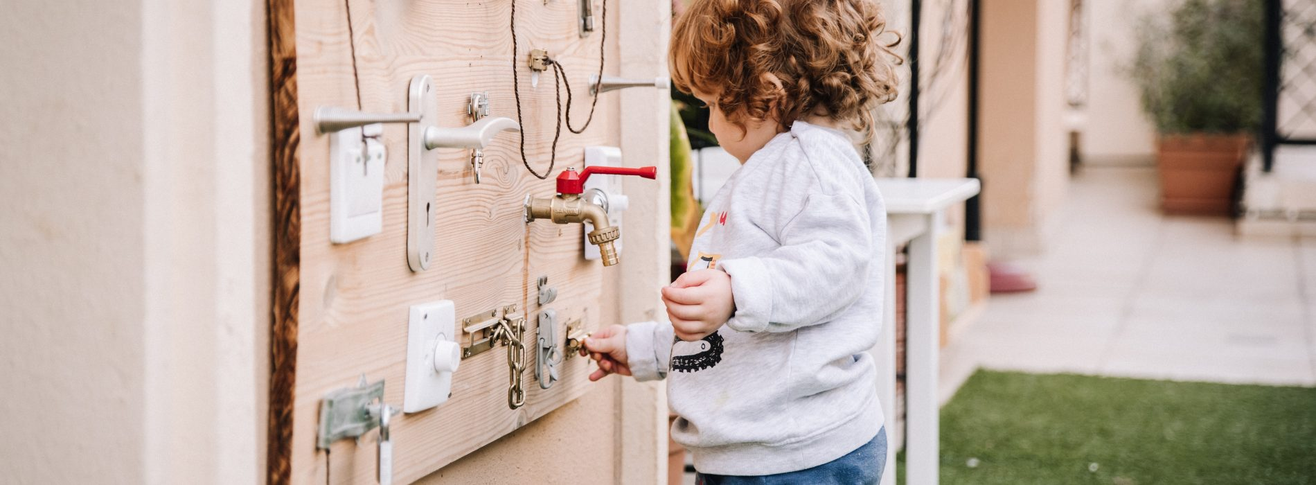 Toddler working at locks and latches board fixed to outside wall