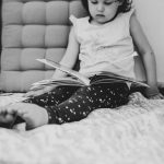 Preschooler concentrating whilst reading book lying in her nap