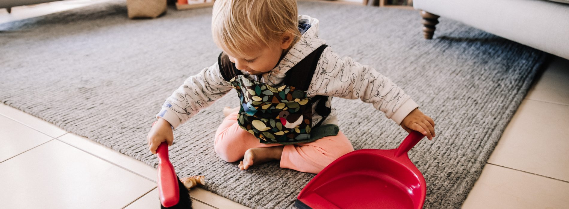 Two year old using dustpan and brush to sweep floor