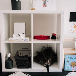 Montessori children's playroom with child size cleaning materials and low bookshelf of books with covers facing forward