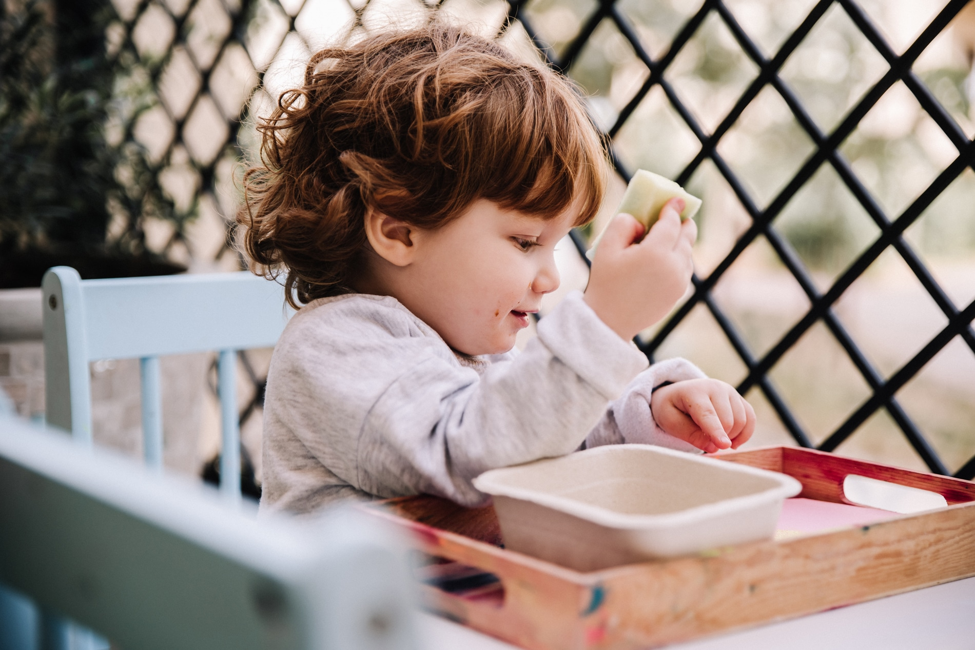 Two year old seated at table doing sponge painting
