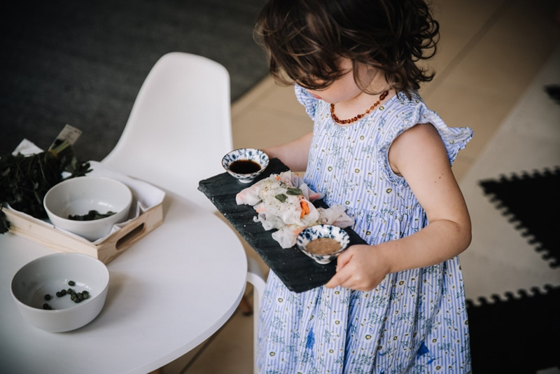 Preschooler carrying a plate of homemade Vietnamese Summer rolls