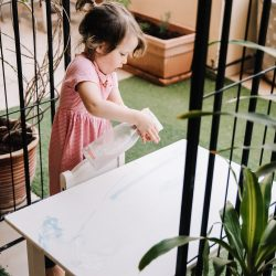 Three year old using spray to clean a table