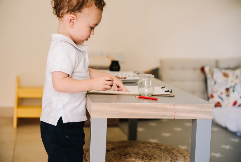 Toddler standing at table drawing