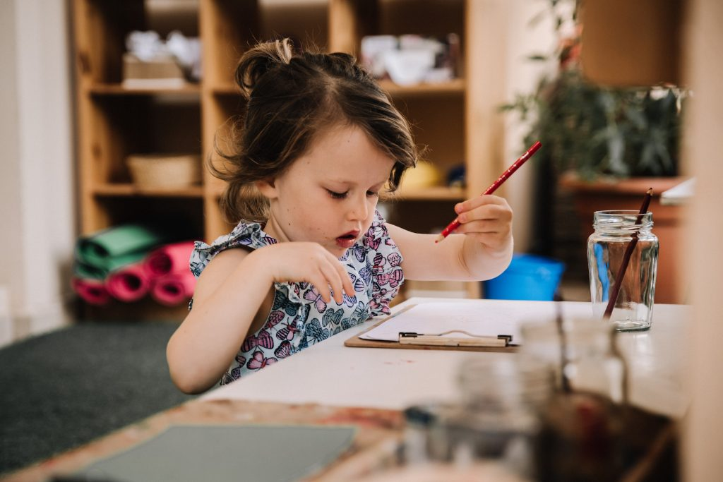 Preschooler focussed on writing with red crayon