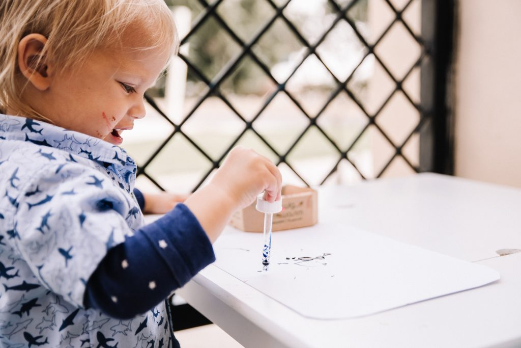 Toddler using dropping pipette with food colouring on white paper