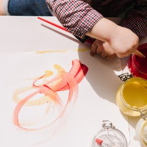Toddler painting with red and yellow paints on white paper