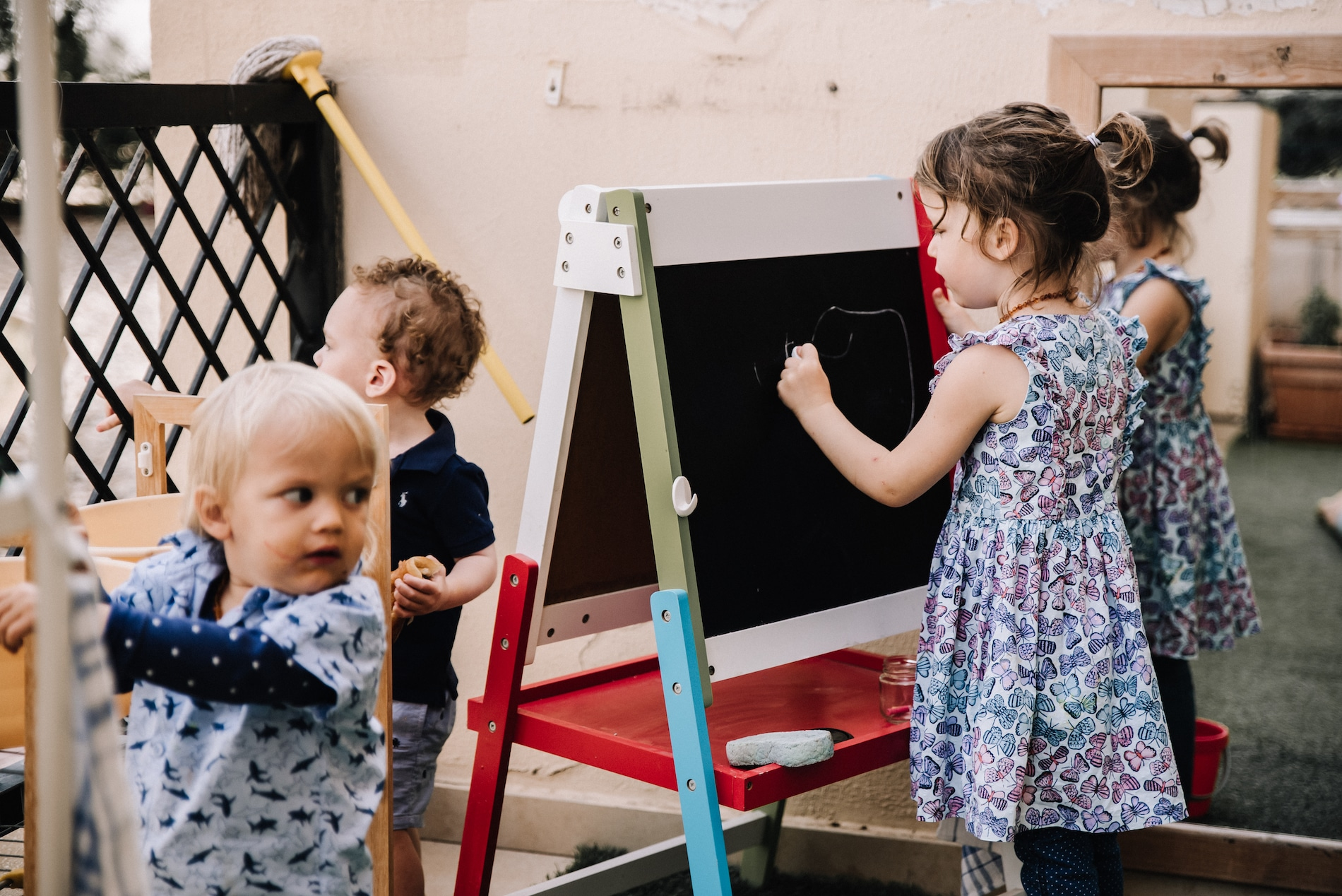 Preschooler drawing on easel with two toddlers close by
