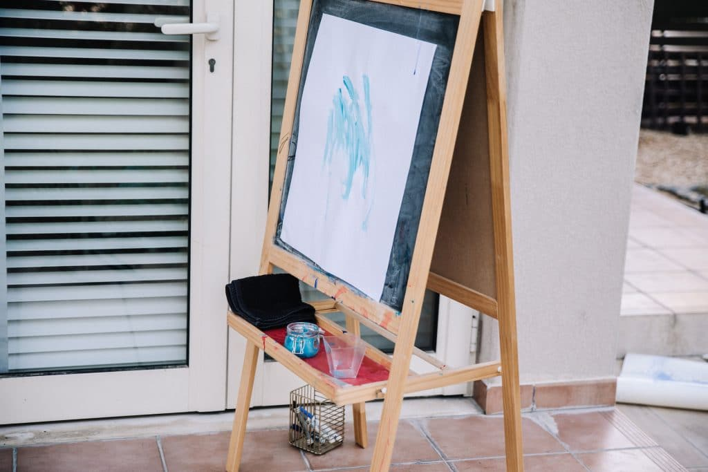 Painting with blue paint stuck onto child's easel on terrace