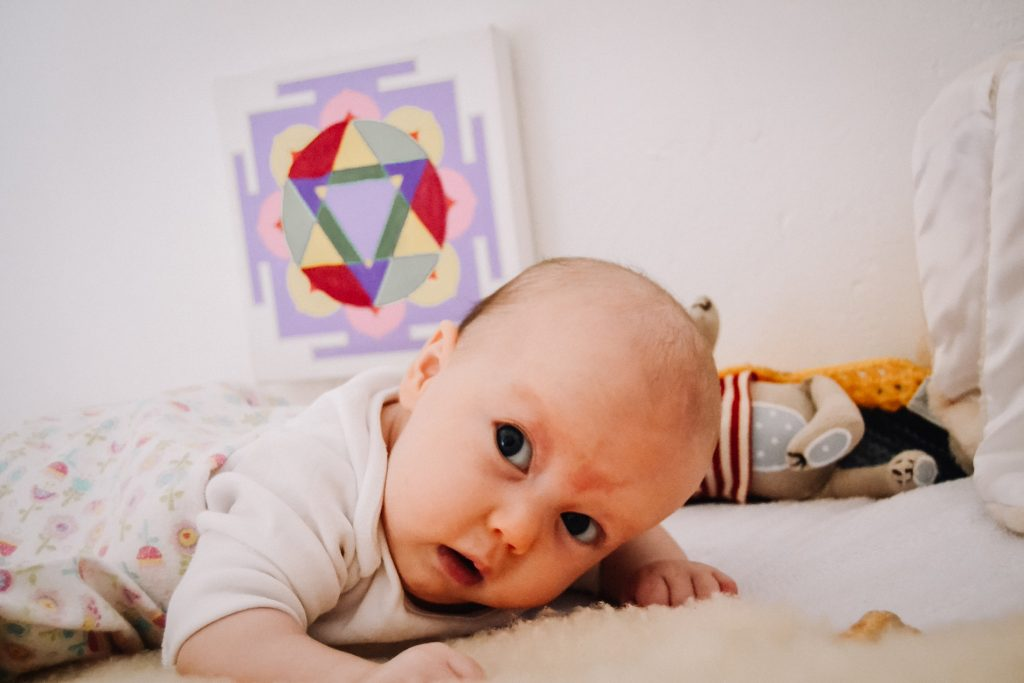 Mandala on wall with two month old baby lying on tummy looking up