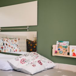 Children's playroom reading area with low bookshelf with book covers facing forward