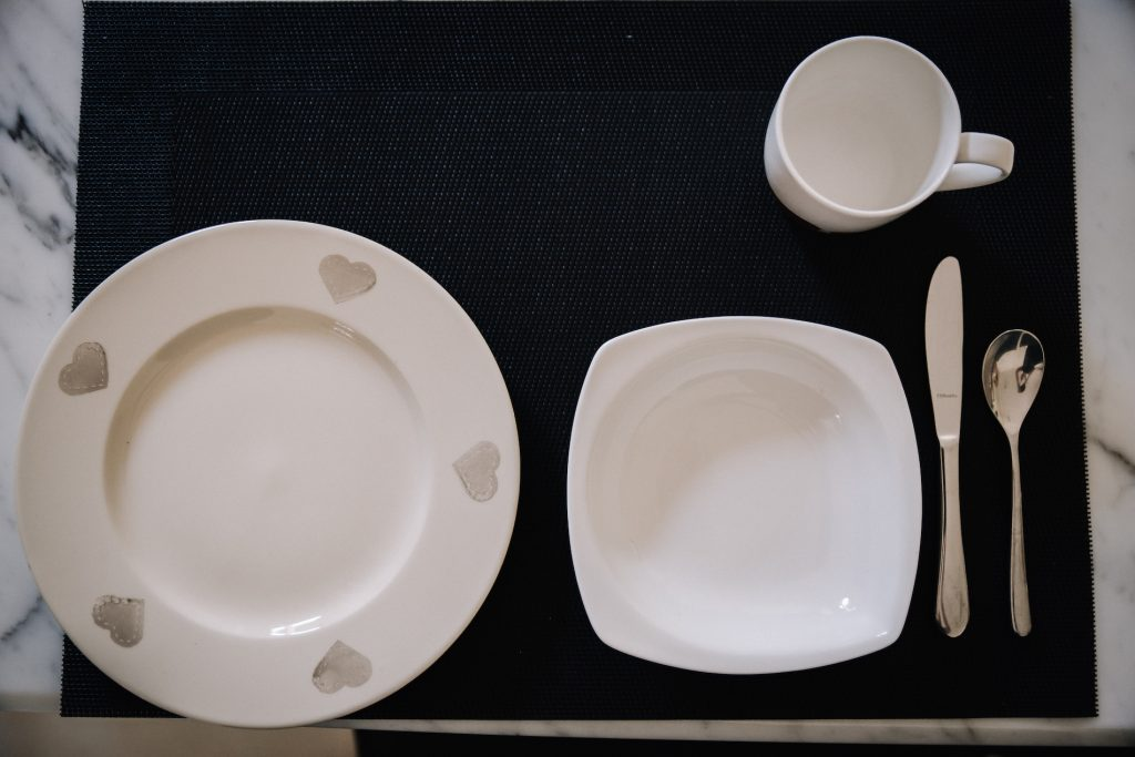 Place setting with ceramic child-sized plate, bowl, cutlery and mug