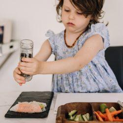 Preschooler sitting at table grinding pepper onto Vietnamese summer roll