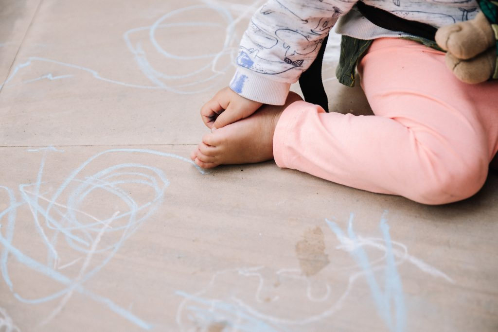 Two year old writing in chalk on the floor