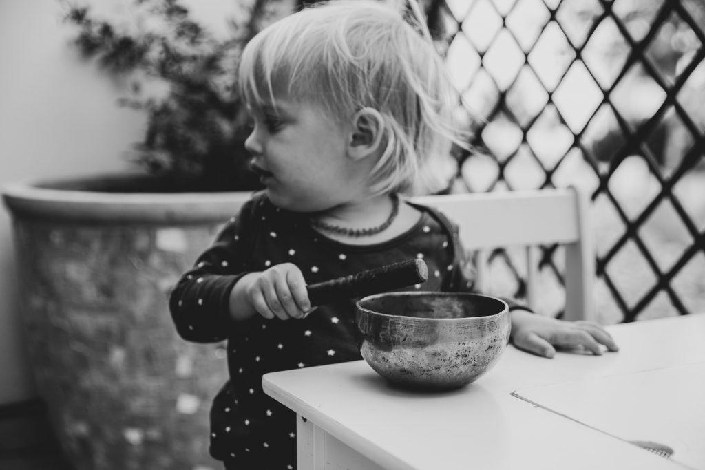 Toddler striking Tibetan singing bowl