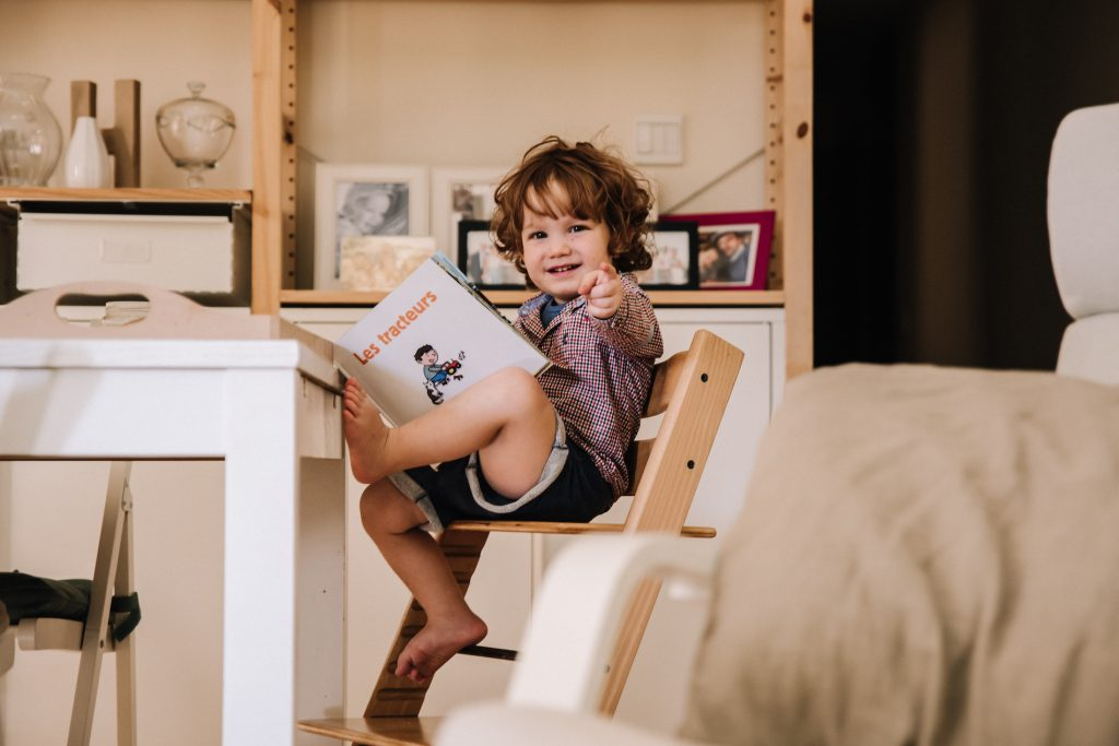 Toddler laughing and pointing at the camera as he reads a book