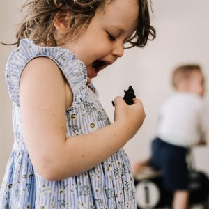 Preschooler laughing as she growls at animal figurine