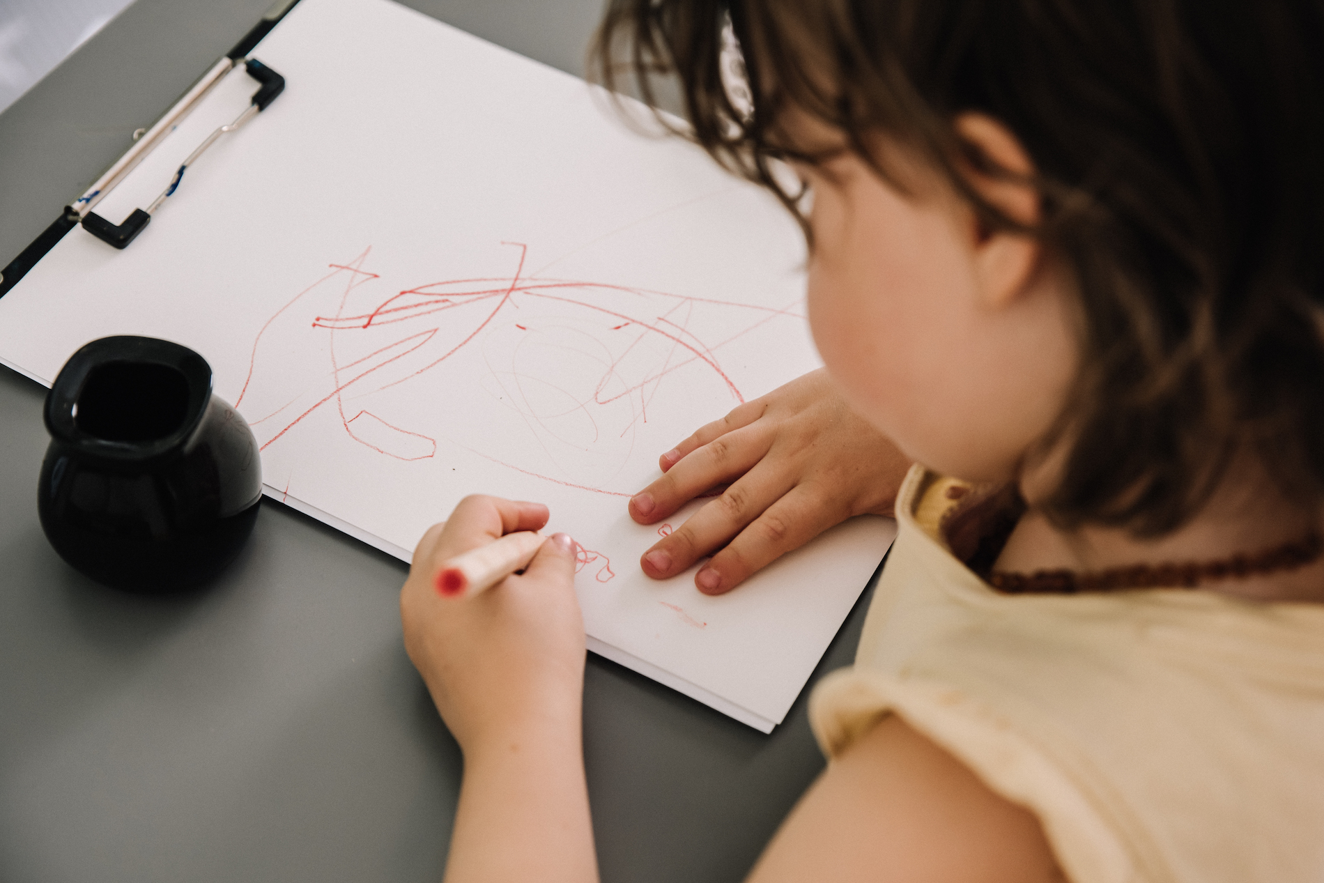 Three year old writing using a pen