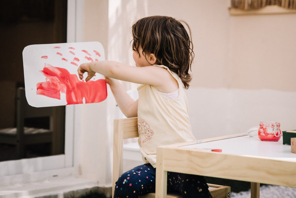 Three year old showing picture she has painted