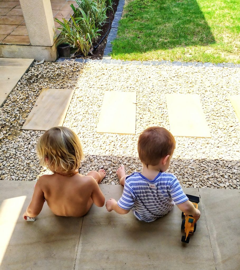 Two year olds sitting side by side with each playing with a toy
