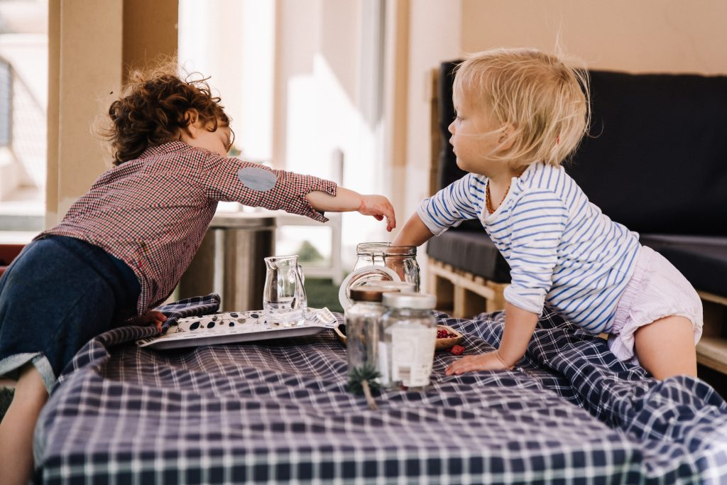 Two toddlers both reaching into jar of fruit