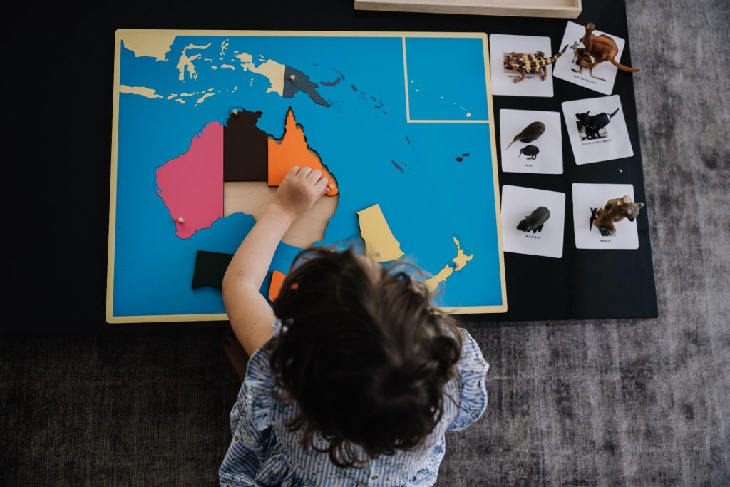 Preschooler doing puzzle map of Australasia