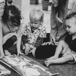 Three young children reading a book with an adult