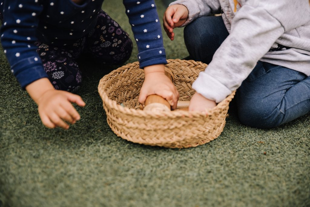 Toddlers choosing musical instruments from a basket