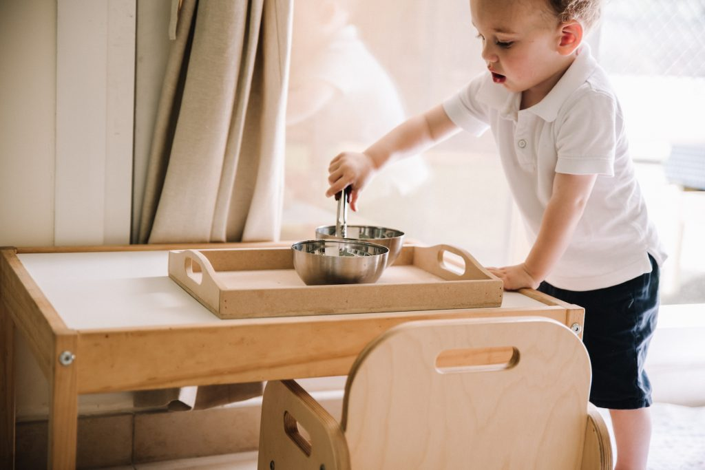 Eighteen month old using tongs to transfer